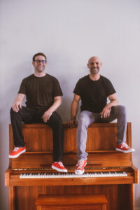 Two musicians smiling and sitting on the piano